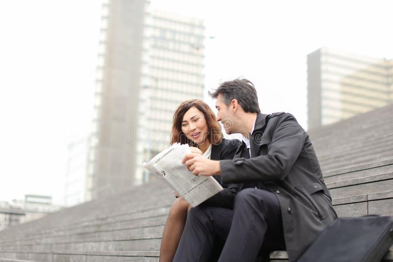 artikel van de ingenieurs het mannelijke en vrouwelijke lezing over bedrijf binnen royalty-vrije stock afbeeldingen
