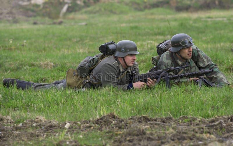 Artillero alemán del soldado de infantería y de máquina con una ametralladora que miente en la hierba Reconstrucción del episodio imagenes de archivo
