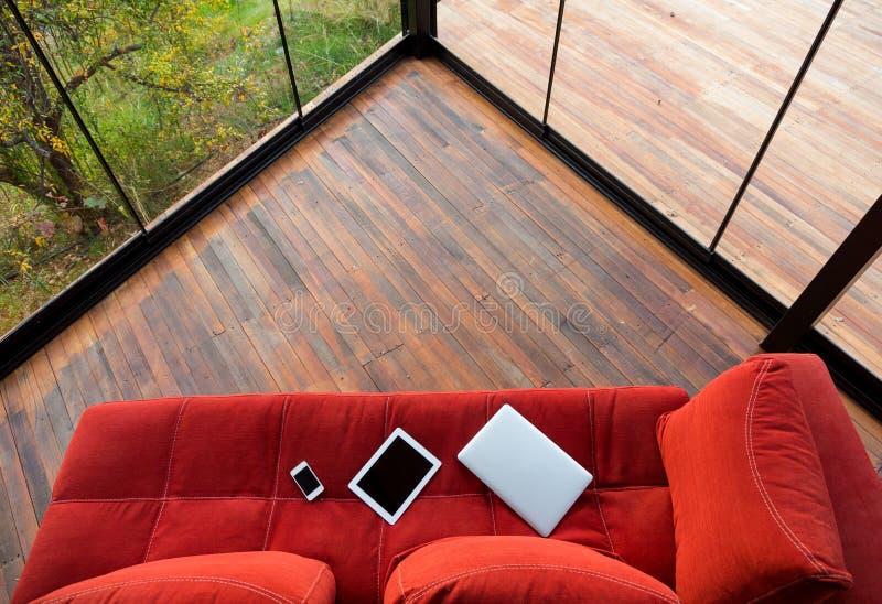 Artilugios electrónicos en el sofá rojo en la esquina de la casa de planta baja de madera fotos de archivo libres de regalías