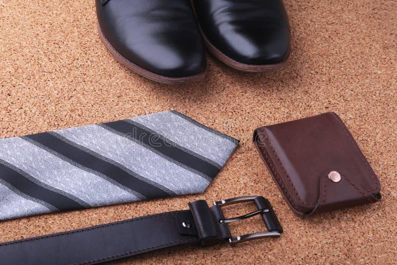 Artilugios y accesorios para los hombres en fondo de madera ligero Correa de moda de los hombres s, cartera, encendedor, frasco i imagen de archivo