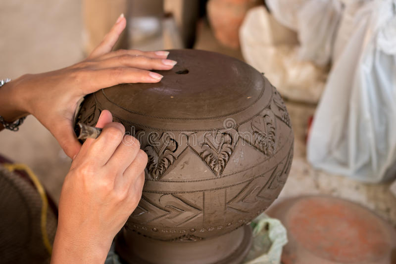Artisan's hands engraving patterns on clay pot in workshop, traditional Asian earthenware production. stock image