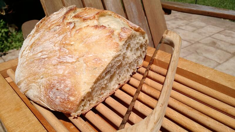 Artisan baked bread with slicer royalty free stock image