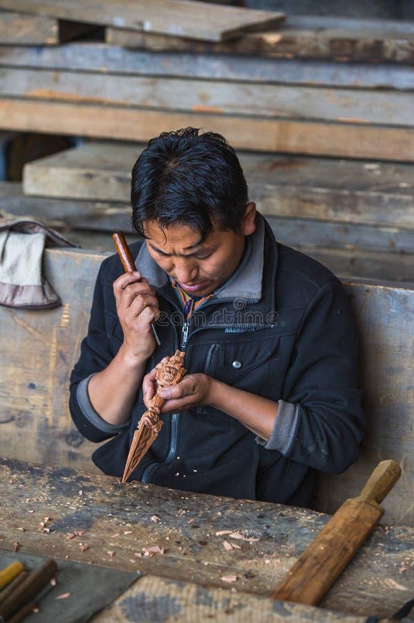 Artisan bhoutanais découpant un vajra en bois avec le couteau, Bhutan images libres de droits