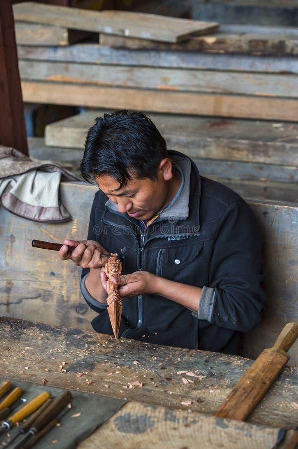 Artisan bhoutanais découpant un vajra en bois, Bhutan images stock