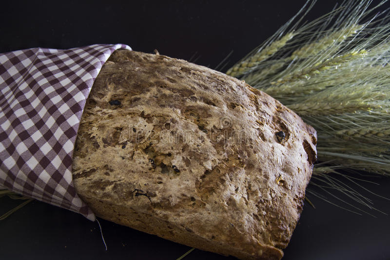 Artisan bread with ears of wheat. Homemade gluten-free and without yeast artisan bread close-up with ears of barley wrapped in checkered napkin royalty free stock photo
