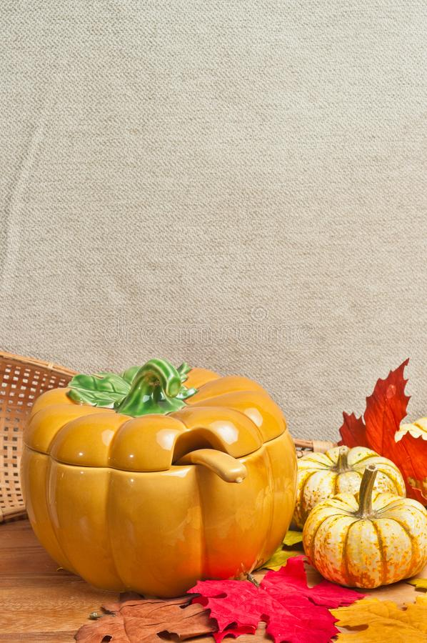Artisan ceramic pumpkin soup bowl with fall leaves on wood board royalty free stock images