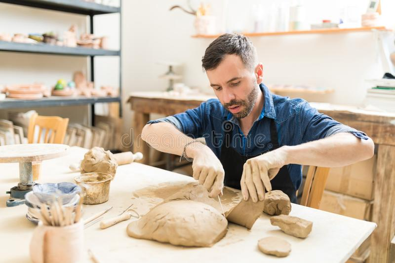 Artisan Cutting And Shaping Clay At Table In Pottery Studio stock photography