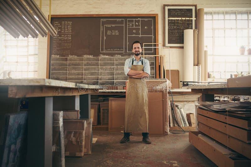 Artisan de concepteur se tenant avec confiance dans son atelier photo stock