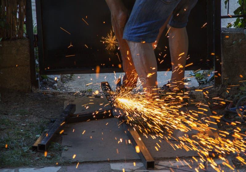 Artisan de travailleur coupant le métal avec la broyeur images libres de droits