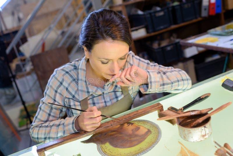 Artisan féminin de portrait peignant l'icône religieuse dans l'atelier photo libre de droits