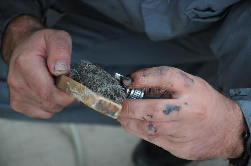 Artisan hold steel brush and cleaning stock photography