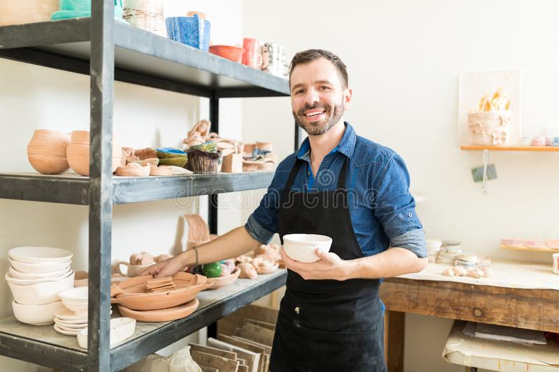 Artisan Holding Clay Bowl By Shelves In Pottery Workshop. Confident male artisan holding clay bowl while standing by shelves in pottery workshop royalty free stock image