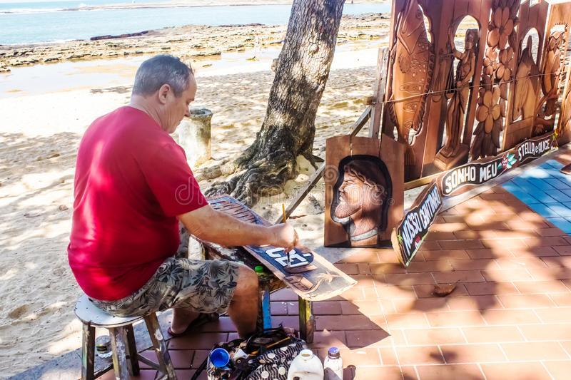 The artisan Itamar carving and selling his pieces by the sea in Guarapari, Brazil. The craftsman Itamar, manufacturing and selling his wooden pieces by the sea royalty free stock photos