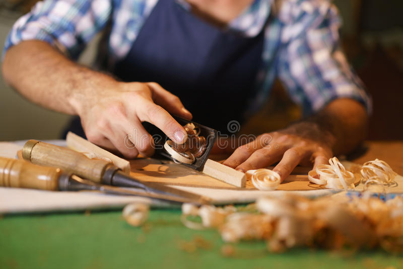 Artisan Lute Maker Chiseling Stringed Instrument Classical Guitar. Lute maker shop and acoustic music instruments: young adult artisan cutting and chiseling wood royalty free stock photos