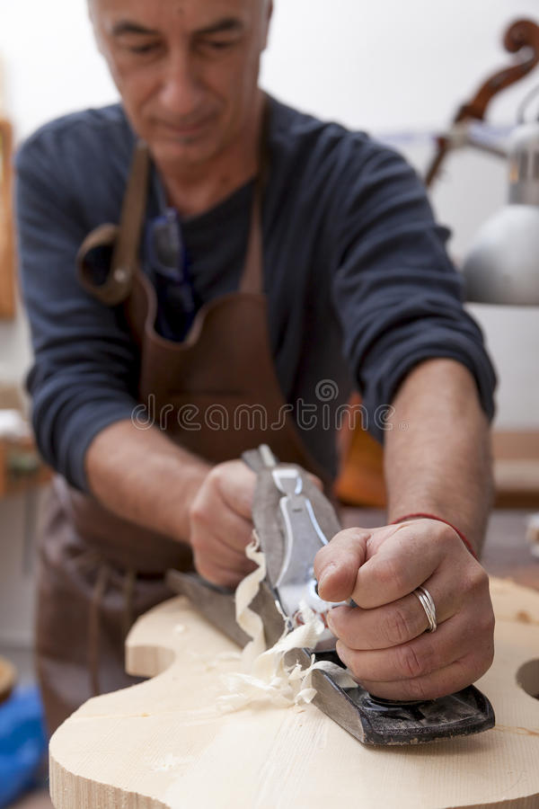 Artisan lutemaker working a violin stock images