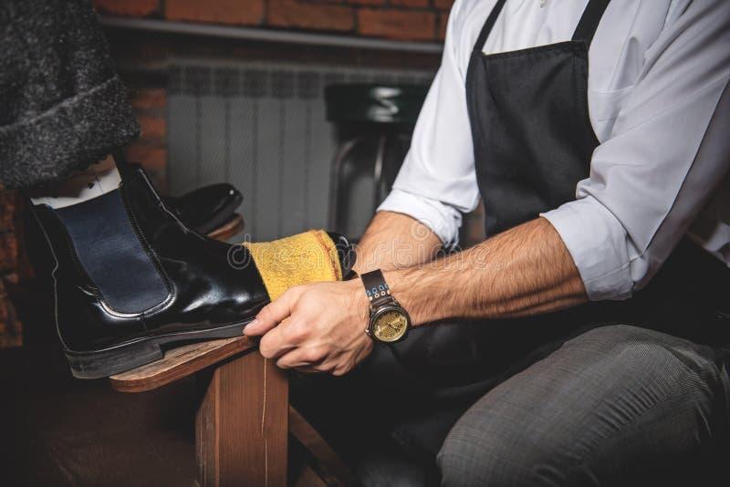 Artisan& x27; mão de s que limpa as sapatas de couro foto de stock