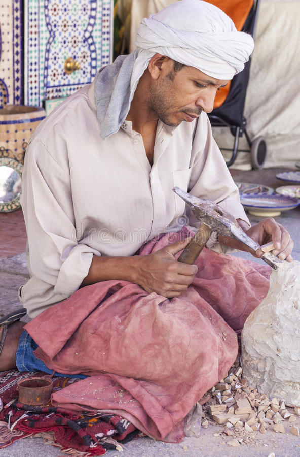 Artisan makes pieces for mosaic craftwork. Badajoz, Spain - September 24, 2016: Artisan makes pieces for mosaic craftwork. He is shaping pieces from glazed tiles royalty free stock photos