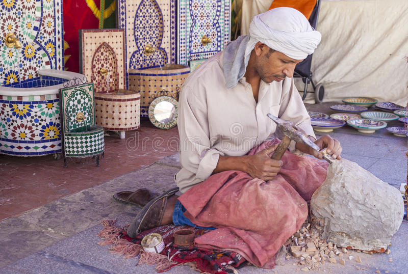 Artisan makes pieces for mosaic craftwork. Badajoz, Spain - September 24, 2016: Artisan makes pieces for mosaic craftwork. He is shaping pieces from glazed tiles stock photography