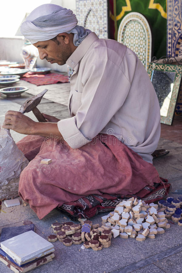 Artisan makes pieces for mosaic craftwork. Badajoz, Spain - September 24, 2016: Artisan makes pieces for mosaic craftwork. He is shaping pieces from glazed tiles stock images