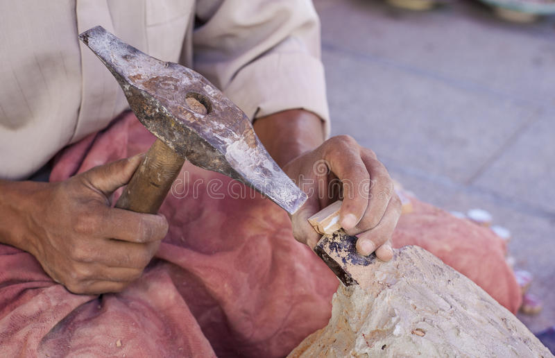 Artisan makes pieces for mosaic craftwork. He is shaping pieces from glazed tiles stock photos