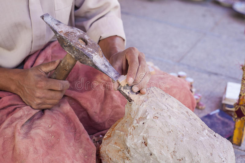 Artisan makes pieces for mosaic craftwork. He is shaping pieces from glazed tiles royalty free stock photography