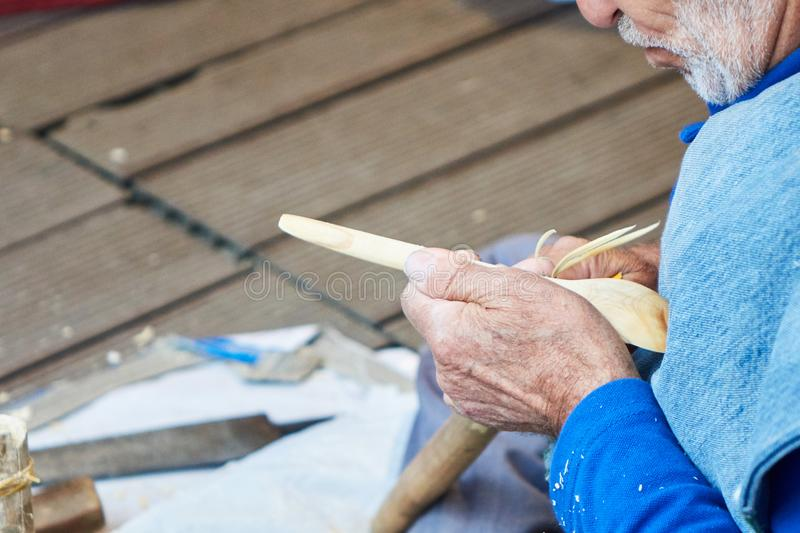The artisan makes a spoon of wood stock photography