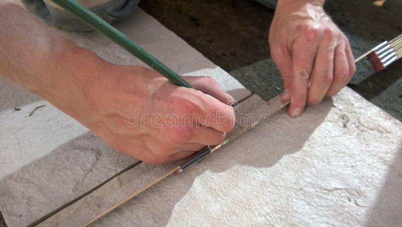 Artisan mesurant des tuiles avec une bande de mesure et un crayon photographie stock libre de droits
