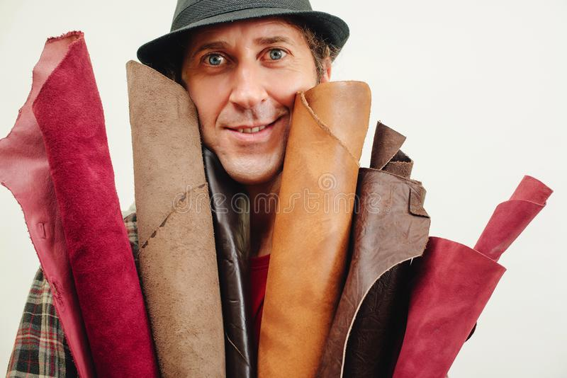 Artisan in a retro hat, holds set of leather in his workshop. Business and entrepreneur concept. Master has idea for new leather. Products stock photo