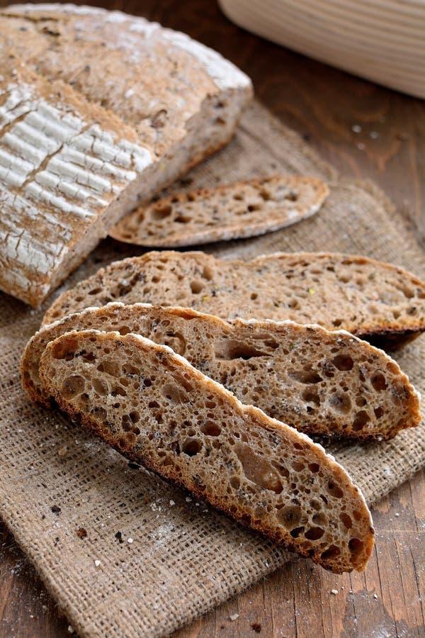 Artisan sourdough bread on sackcloth. Artisan sourdough bread cutted in slices on sackcloth. Wooden background royalty free stock images