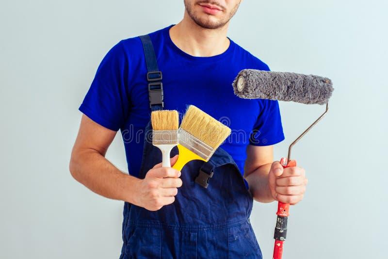 Artisan tenant le rouleau et les brosses de peinture images stock