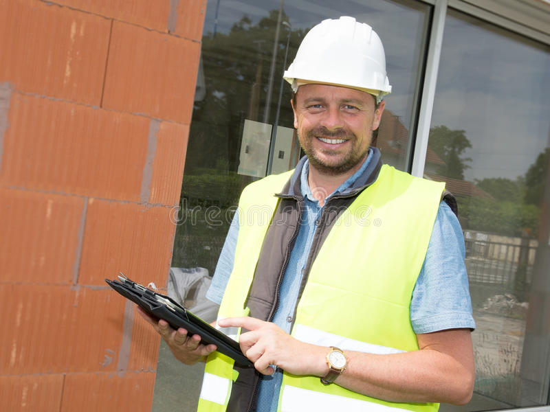 Artisan using his tablet computer in a construction site stock images