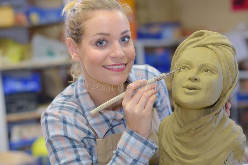 Artisan woman finishing sculpture in studio royalty free stock photos