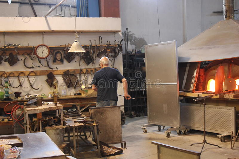 Artisan at work ina Furnace. Murano, Italy: An artisan at work making glass sculpture in its furnace near Venice royalty free stock image