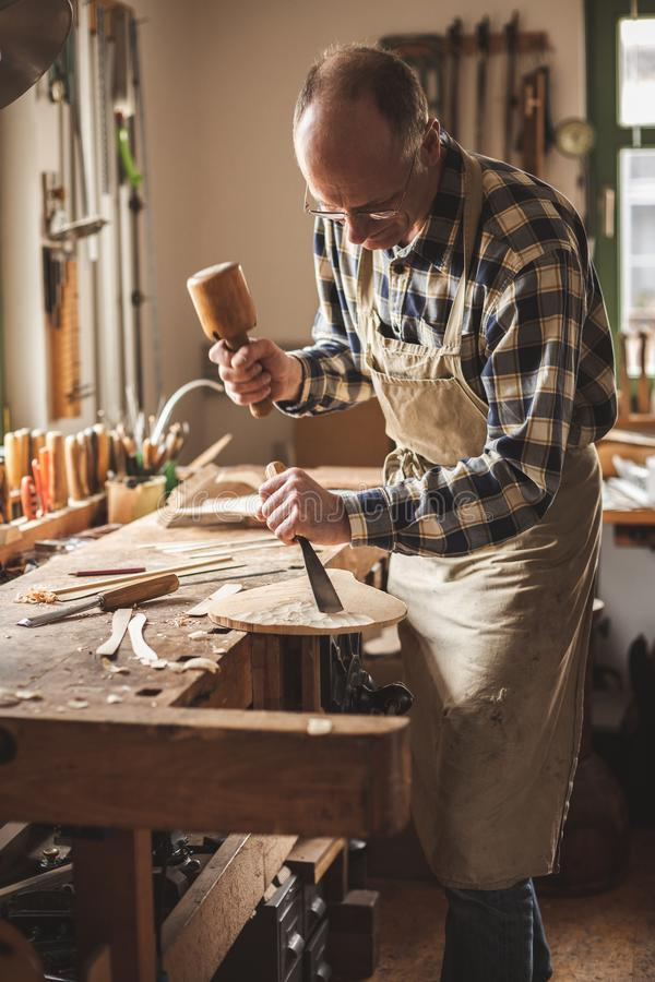 Artisan working inside a traditional workshop. Mature instrument maker is working with a mallet and a chisel inside his traditional workshop. Good view of the royalty free stock photo