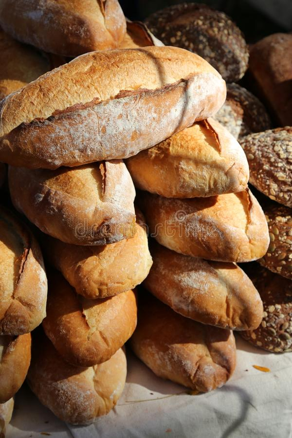 Artisanal bread loaves stacked on table. Crusty artisanal loaves of bread stacked on a table. Crunchy crust fresh baked stock image