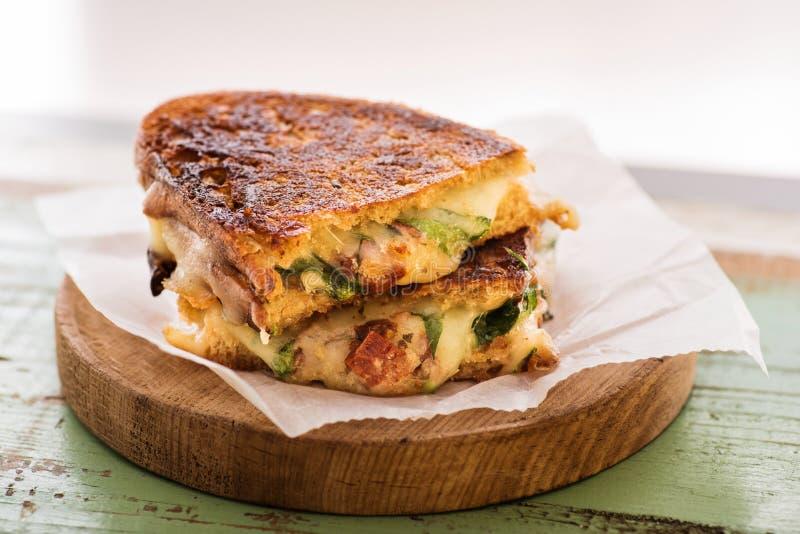 Artisanal smörgås som göras med ost, bacon och ny sallad arkivbilder