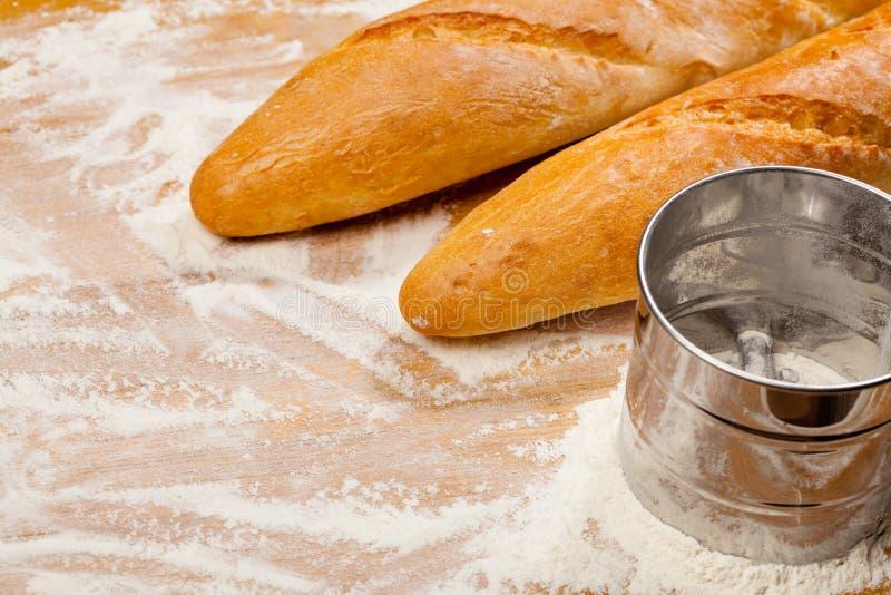 Artisanale Franse baguettes en bloemzeef of zeefje op een lijst royalty-vrije stock fotografie