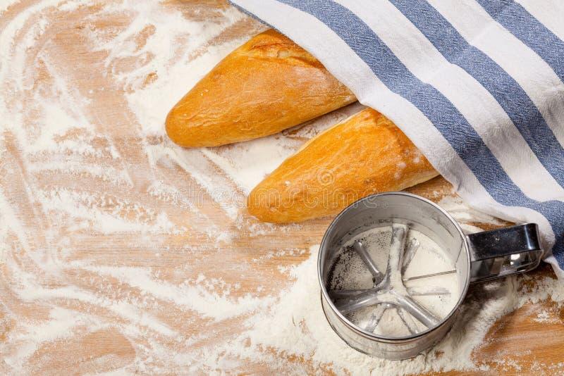 Artisanale Franse baguettes en bloemzeef of zeefje op een lijst royalty-vrije stock foto's