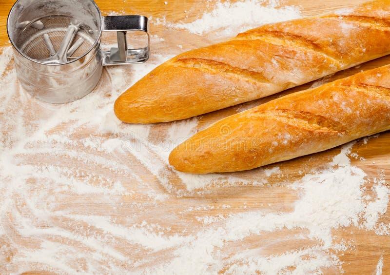 Artisanale Franse baguettes en bloemzeef of zeefje op een lijst stock foto