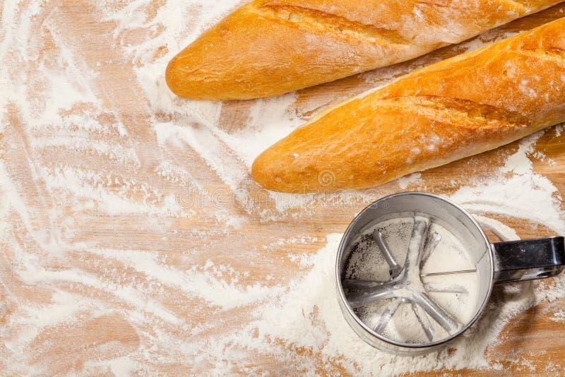 Artisanale Franse baguettes en bloemzeef of zeefje op een lijst royalty-vrije stock afbeelding