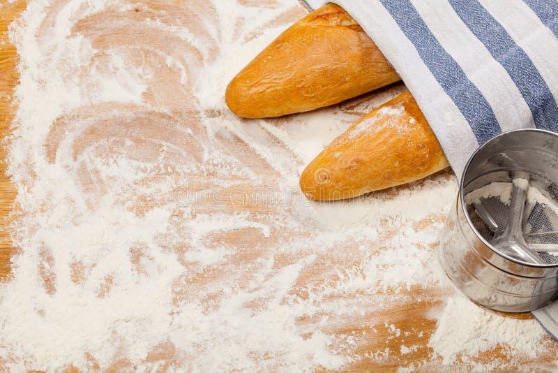 Artisanale Franse baguettes en bloemzeef of zeefje op een lijst stock afbeelding
