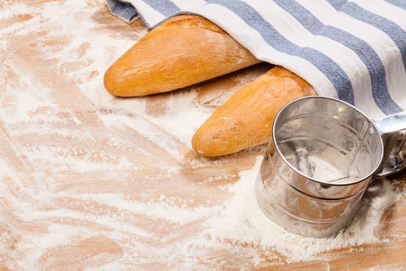 Artisanale Franse baguettes en bloemzeef of zeefje op een lijst stock fotografie