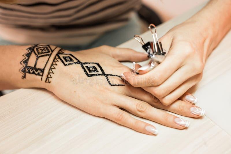 Mehndi Tattoo For Hand : Artist applying henna tattoo on women hands. mehndi is traditional