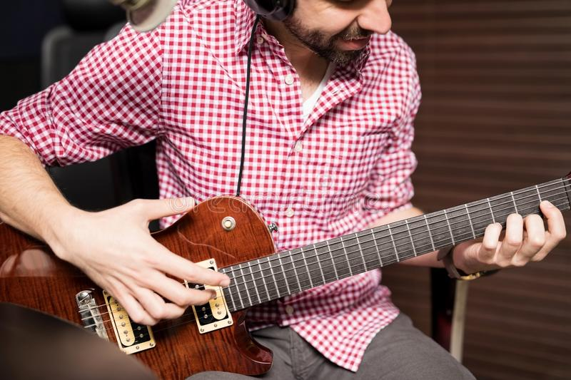 Artist broadcasting live music on air. Close up of male artist playing guitar at radio station, broadcasting live music on air stock photos