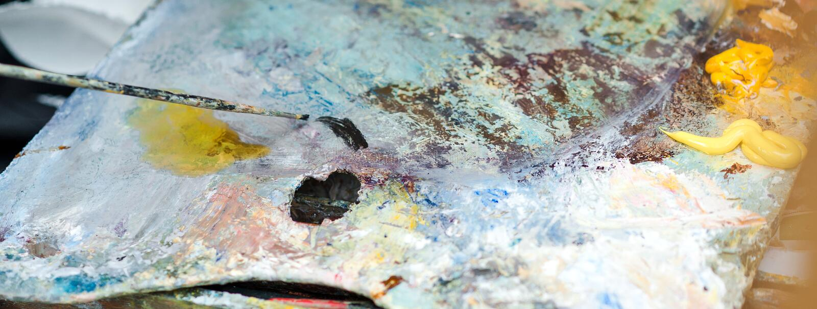 Artist brush mix paints with brush on palette. Artist studio. Palette with paintbrush. Artist paints a picture of oil paints. Art. Palette. Primary acrylic stock photos