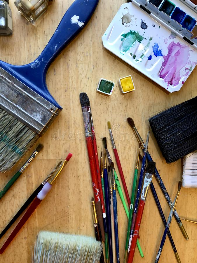 Artist brushes and paints in top view design, art studio table with pans of watercolor ready for painter, creative workplace royalty free stock image