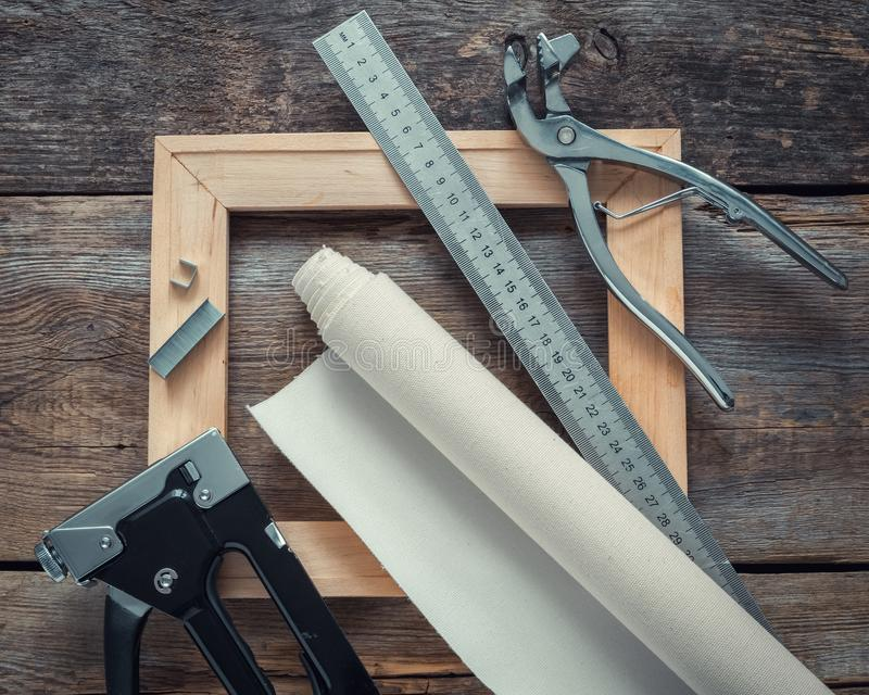 Artist canvas in roll, wooden stretcher bar, canvas pliers, staple gun and ruler. stock images