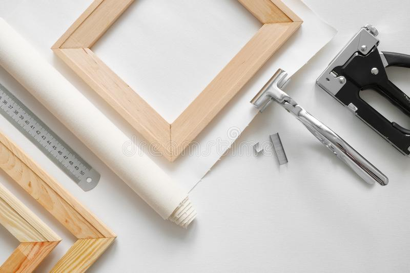 Artist canvas in roll, wooden stretcher bars, canvas stretcher pilers and staple gun. Top view royalty free stock photos
