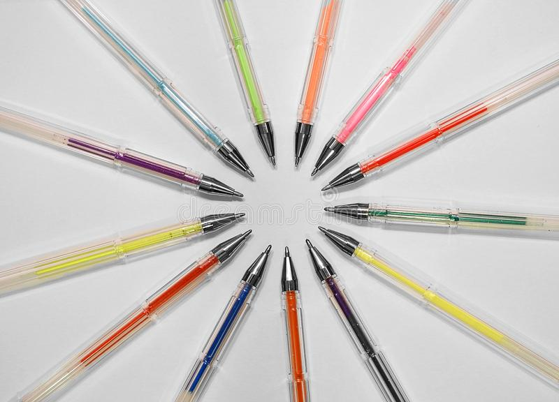 Artist colouring gel pens pencils school drawing ink. Photo of artists colouring gel pens arranged in a circle on white art card ideal for school university stock photography