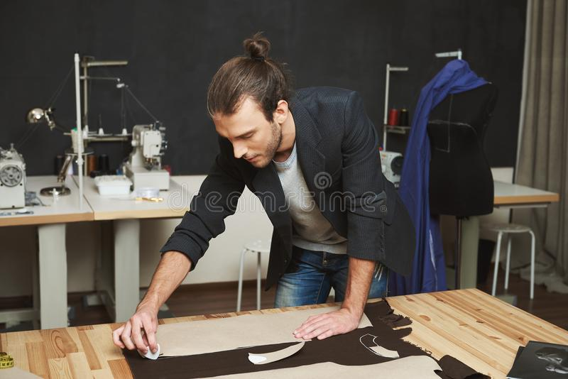 Artist creating masterpiece. Close up of young beautiful male clothes designer with trendy hairstyle and fashionable. Clothes working on new dress with stock photo
